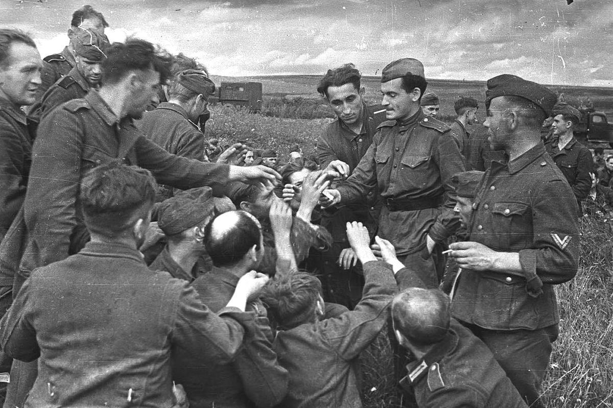 二战1943年,苏联士兵在给德国战俘分发香烟.图片