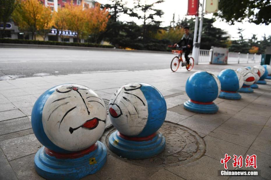 和石头墩变身成哆啦A梦、小黄人、喜羊羊等卡通形象吸引市民.据图片