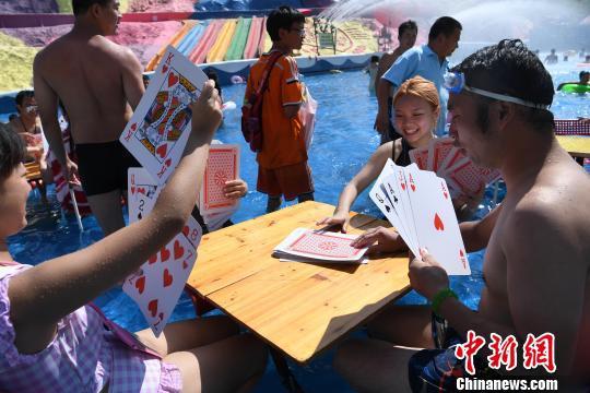 重庆民众水中玩巨型扑克牌消暑