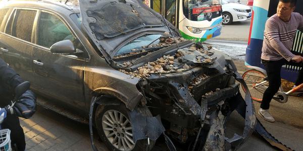 路面地下管线突爆裂 崩出泥石砸坏车辆